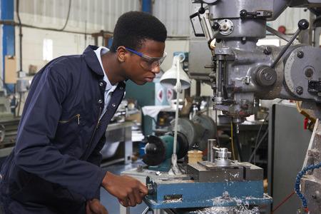 afroamericanas: Masculino Ingeniero Aprendiz Que Trabajan Taladro En Fábrica
