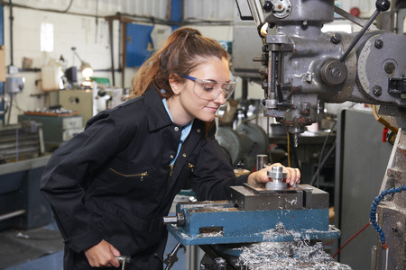 Female Apprentice Engineer Working On Drill In Factory Stockfoto