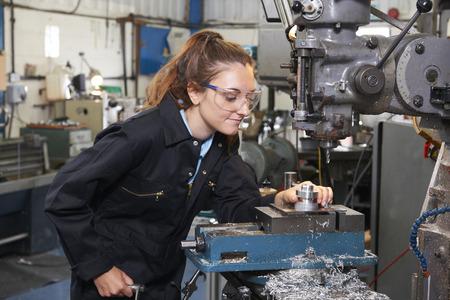 Female Apprentice Engineer Working On Drill In Factory Standard-Bild