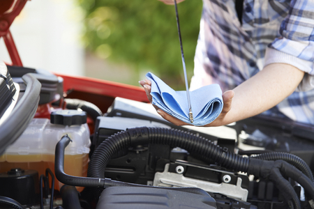 Close-Up Of Woman Checking Car Engine Oil Level On Dipstick Stockfoto