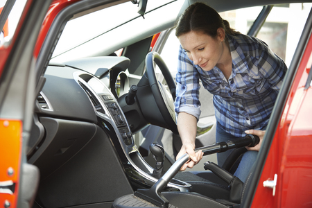 clean car: Woman Cleaning Interior Of Car Using Vacuum Cleaner