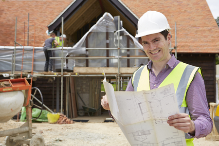 house coats: Architect On Building Site Looking At House Plans Stock Photo