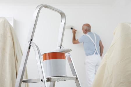 pintor: El hombre de habitaciones que adorna con el bote de pintura y el pincel en primer plano
