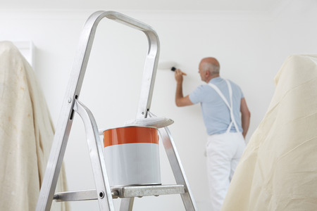 painter: Man Decorating Room With Can Of Paint And Brush In Foreground