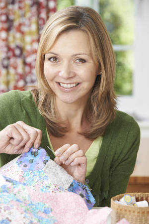 sewing cotton: Portrait Of Woman Sewing Quilt At Home