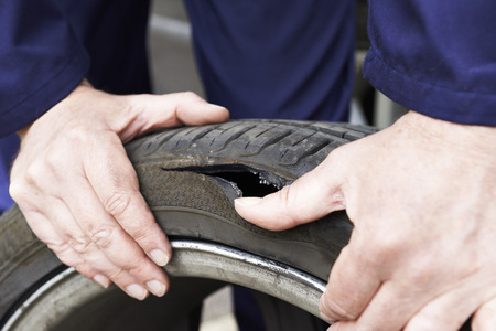 inflating: Close Up Of Mechanic Examining Damaged Car Tyre