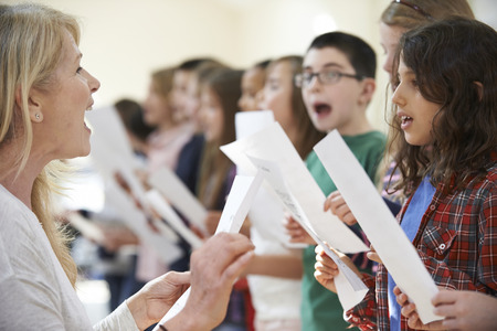 child singing: Children In Singing Group Being Encouraged By Teacher