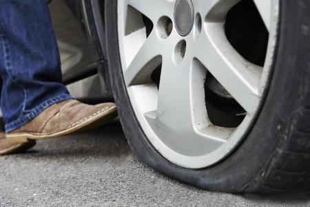 llantas: Motorista Kicking Rueda pinchada en el coche Foto de archivo