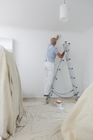 Man On Ladder Decorating Domestic Room With Paint Brush 版權商用圖片
