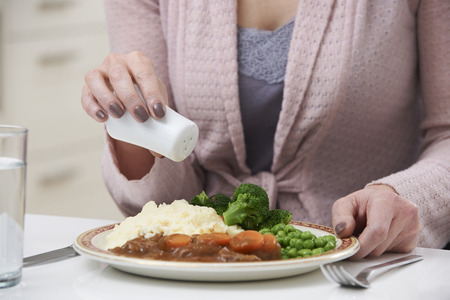 salt shaker: Woman At Home Adding Salt To Meal