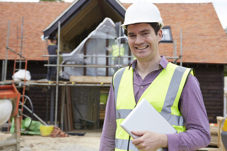 site manager: Architect On Building Site Using Digital Tablet