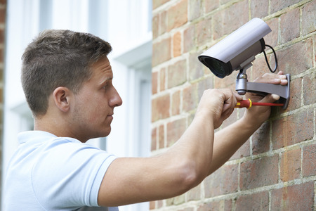 security equipment: Security Consultant Fitting Security Camera To House Wall