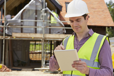 construction manager: Architect On Building Site Using Digital Tablet