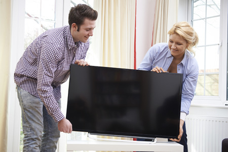 television: Excited Couple Setting Up New Television At Home