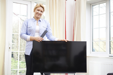unwrapping: Portrait Of Proud Woman With New Television At Home Stock Photo