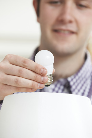 low energy: Man Putting Low Energy LED Lightbulb Into Lamp At Home
