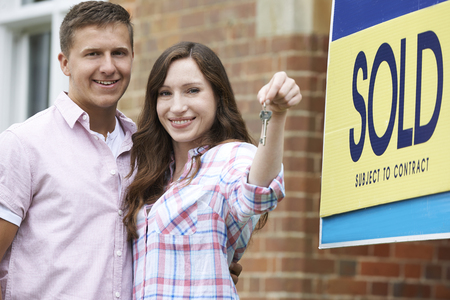 sold sign: Excited Couple Outside New Home Holding Keys