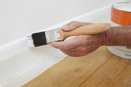hand up: Close Up Of Man Painting Skirting Board