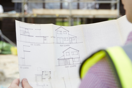 building blueprint: Architect On Building Site Looking At Plans For House