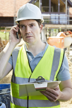 quality work: Construction Worker On Building Site Using Mobile Phone