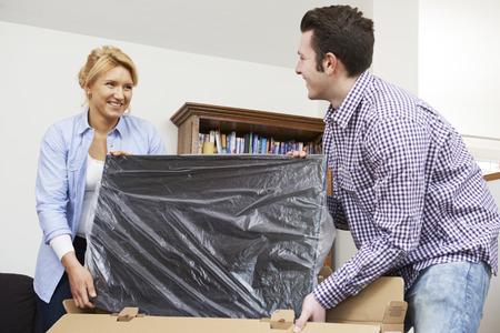 personas ayudando: Pareja Desembalaje Nueva televisión en casa