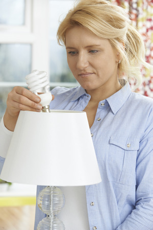 energy use: Woman Putting Low Energy Lightbulb Into Lamp At Home