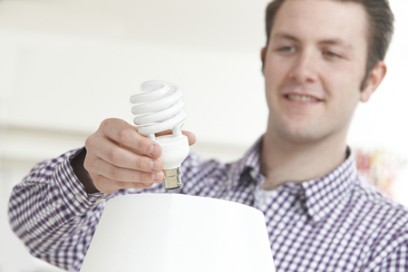 florescent light: Man Putting Low Energy Lightbulb Into Lamp At Home Stock Photo