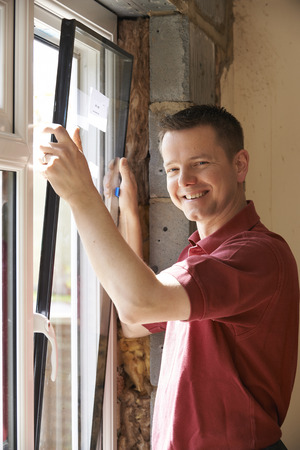 replacement: Construction Worker Installing New Windows In House Stock Photo