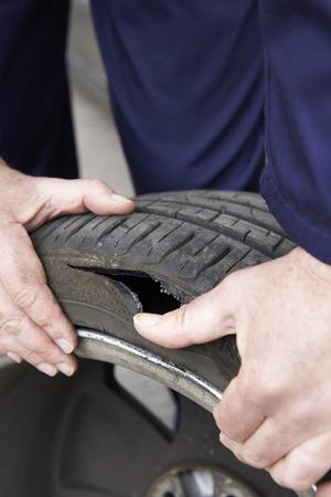 puncture: Close Up Of Mechanic Examining Damaged Car Tyre