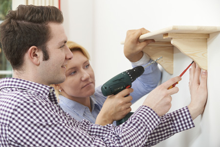 putting up: Couple Putting Up Wooden Shelf Together At Home