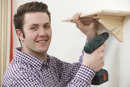 putting up: Man Putting Up Wooden Shelf At Home Using Electric Drill