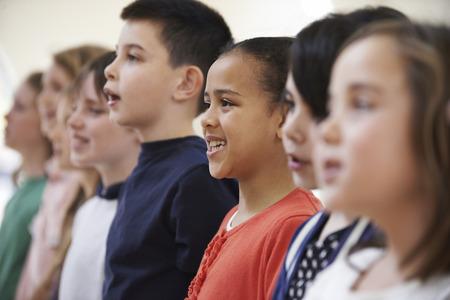 kinderschoenen: Groep schoolkinderen zingen in koor Together Stockfoto