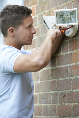 light fitting: Security Consultant Fitting Security Light To House Wall