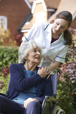 the ageing process: Carer Pushing Senior Woman In Wheelchair