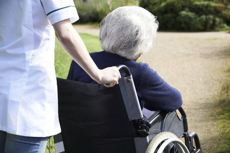 persona de la tercera edad: Cierre De cuidador empuja a la mujer mayor en silla de ruedas