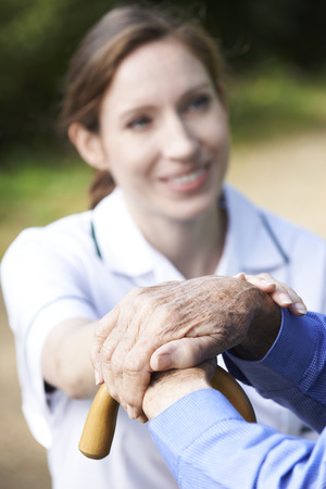 Hospital care: Senior Mans Hands Resting On Walking Stick With Care Worker In Background
