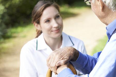 apoyo social: Manos de descanso del hombre mayor en recorrer Trabajador Care Palo Con En El Fondo