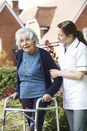 the ageing process: Carer Helping Senior Woman To Walk In Garden Using Walking Frame