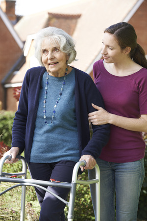 smiling people: Daughter Helping Senior Mother To Use Walking Frame