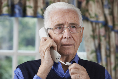 answering phone: Worried Senior Man Answering Telephone At Home