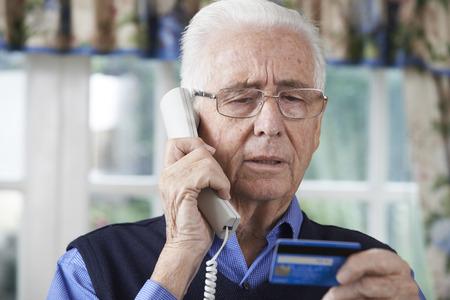 confundido: Hombre mayor que da detalles de tarjeta de crédito en el teléfono Foto de archivo