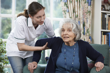 levantandose: Cuidado del trabajador a la mujer mayor que levantarse de la silla
