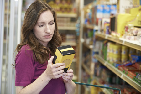 shopping binge: Woman Checking Labelling On Box In Supermarket Stock Photo