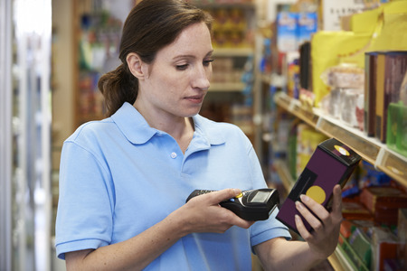 sales assistant: Sales Assistant Checking Stock Levels In Supmarket Using Hand Held Device Stock Photo