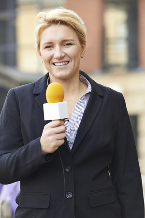 broadcasting: Female Journalist Broadcasting Outside Office Building Stock Photo