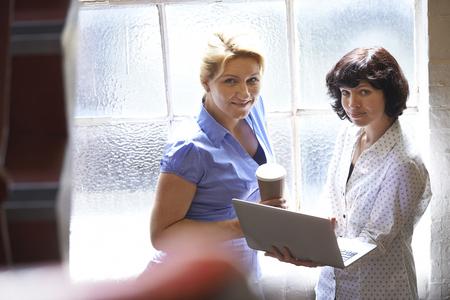 informal clothing: Two Businesswomen Having Informal Meeting In Office