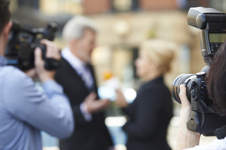 Photographer Taking Pictures Of Female Journalist Interviewing Businessman Stock Photo