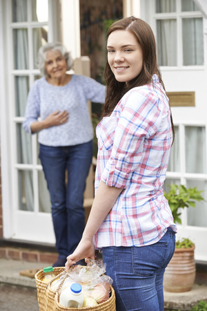community people: Teenage Girl Doing Shopping For Senior Woman