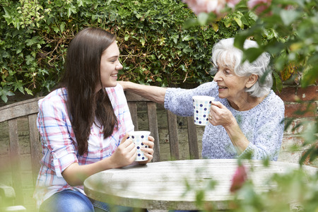 tea hot drink: Teenage Granddaughter Relaxing With Grandmother In Garden Stock Photo