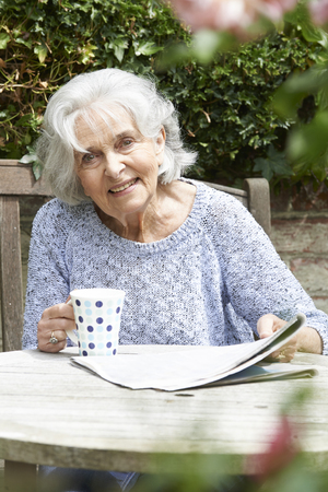 coffee mugs: Portrait Of Senior Woman Relaxing In Garden Reading Newspaper Stock Photo